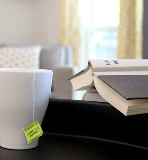White mug with tea next to open book - The ONE must-have-item for your Airbnb listing